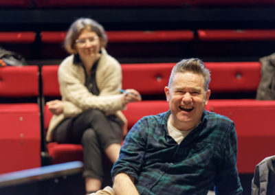 Director and colleague laughing, watching rehearsal